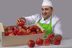 Fruit seller with box of apples Stock Photos