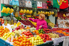 Fruit seller organizing and taking care of the stand in the interior of the historical Bolhao Market. Porto, Portugal. December 29, 2014: Fruit seller organizing Royalty Free Stock Image