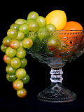 Fruit set. Vase with tropical fruit is on the table isolated on black background Stock Images