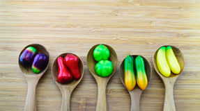 Fruit-shape desserts made of mung-bean flour with natural colour. Ing on the wooden spoon with wood background. It is one of a famous Thai dessert royalty free stock images
