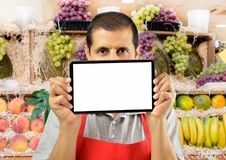 Fruit shop assistant is holding the tablet. Shopman holding tablet covering his mouth with copyspace over at the fruits store Stock Photography