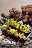 Fruit skewers and chocolate candies. Inside, indoors, interiors, food, meal, nutrition, nourishment, vegetarian, fondue, candy, bar, sweet, unhealthy, calories stock photo