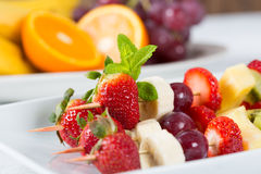 Fruit skewers. Delicious natural grape skewers strawberries kiwi banana Royalty Free Stock Images
