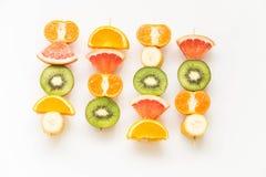 Fruit skewers on the white background. Fruit skewers on the bright background / the concept of healthy lifestyle Royalty Free Stock Photo