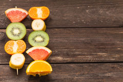 Fruit skewers on the wooden background / the concept of healthy lifestyle with place for text Stock Images