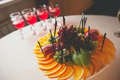 Fruit sliced in a large assortment on skewers lie on a white plate. Next to the glasses of juice on a light wooden table. royalty free stock image