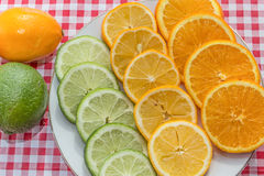 Fruit. Sliced lemons, limes and oranges on red and white checkered background Stock Photos