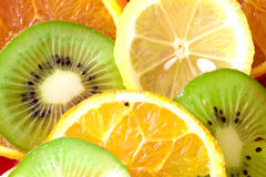 Fruit slices (lemon, kiwi, tangerine, orange). Ripe fruit slices overlapped background (lemon, kiwi, tangerine, orange) Studio shot royalty free stock image