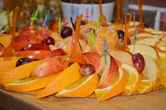 Fruit slicing of orange and apple with colored plastic skewers on cocktail or a buffet table royalty free stock photos
