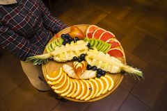 Fruit slicing on a tray. In the hands of a waitress Stock Image