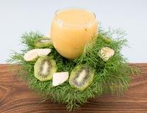 Fruit smoothie of banana, orange, kiwi and tangerine in the glass Stock Photo