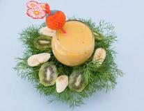 Fruit smoothie of banana, orange, kiwi and tangerine in the glass Royalty Free Stock Image
