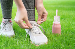 Fruit smoothie and  girl lacing running shoes before workout. Royalty Free Stock Image