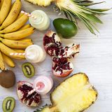 Fruit smoothies of different tastes in glass bottles with ingredients on white wooden surface. Flat lay. From above. Close-up royalty free stock photos