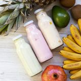 Fruit smoothies of different tastes in glass jars with ingredients on a white wooden surface. Top view, from above. Flat lay, royalty free stock photos
