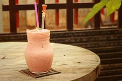 Fruit smoothies in glass placed in the garden. Royalty Free Stock Photo