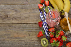 Fruit smoothies in jar. On a wooden background royalty free stock photo