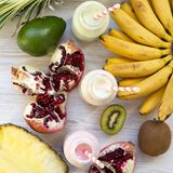 Fruit smoothies or milkshakes of different tastes in glass bottles with ingredients on white wooden surface, top view. Flat lay. royalty free stock photo