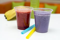 Fruit Smoothies and Straws. Two plastic throwaway glasses of red and purple fruit smoothies with large straws and a banana royalty free stock photography