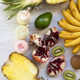 Fruit smoothies of various tastes in glass jars on white wooden surface, top view. Overhead stock photo