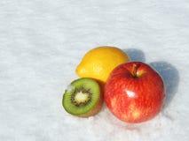 Fruit on Snow. Apple, Lemon and Kiwi on Snow Stock Image
