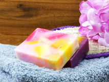 Fruit soap with bath items and towel on wooden background Stock Images