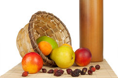 Fruit spill out of the basket on a bed of straw Royalty Free Stock Images