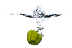 Fruit Splash. Photo of a fresh green bell pepper falling into the water. The photo is isolated on white background. There is a nice splash and bubbles Royalty Free Stock Images