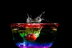 Fruit Splash. Colorful high speed photo of a strawberry splashing in colored water Royalty Free Stock Photos