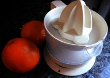Fruit squeezer and two oranges royalty free stock photography