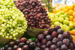 Fruit Stall with Grapes and Plums. Colourful fruit stall with green and red grapes, plums and some mandarins in background. Focus is on plums. Fruits are on Stock Photo