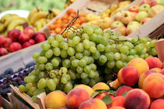 Fruit Stand With Grapes In Market. A fruit stand selling grapes, nectarines, apples, bananas, and other fresh fruit Royalty Free Stock Images