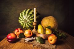 Fruit Still Life. With pears, nectarines, melon, watermelon and candle in a carved candle holder Stock Photos