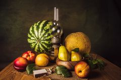 Fruit Still Life. With pears, nectarines, melon, watermelon and an old kerassene lamp Stock Photos