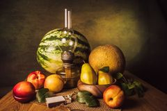 Fruit Still Life. With pears, nectarines, melon, watermelon and an old kerassene lamp Stock Images