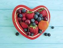 Fruit strawberry, blueberry, cherry, apricot antioxidant detox plate heart on blue wooden. Fruit strawberry blueberry cherry apricot plate heart on blue wooden Stock Photo
