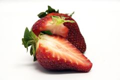 Fruit - Strawberry Cut. Cut fresh strawberry and whole strawberry sit together isolated royalty free stock photo