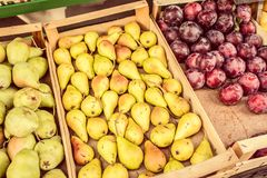 Fruit street market in Italy. Fresh pears and plums. Street fruit market in Italy. Fresh ripe pears and plums in wooden boxes. Sorrento, summer. Food background stock photo