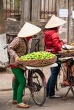 Fruit street vendors with bicycles on the street of Lao Kai, Vie. Tnam-China border. Vietnamese woman street venders with Non La or Vietnam hat. Street food royalty free stock photo