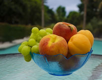 Fruit by the swimmimg pool. Grape, peaches and apricots in glass plate on table by the swimming pool Royalty Free Stock Photography