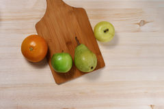 Fruit on the table. Fruits lie on a wooden countertop with a cutting board Royalty Free Stock Photos