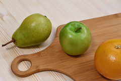 Fruit on the table. Fruits lie on a wooden countertop with a cutting board Stock Photo