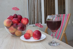 Fruit on the table. Peaches, nectarine, plums. A glass of red  wine Royalty Free Stock Photo