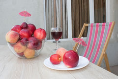 Fruit on the table. Peaches, nectarine, plums. A glass of red  wine Stock Image