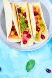 Fruit tacos. Summer snacks. Fruit tacos with orange, kiwi, grapefruit on blue background and berry. Summer snacks. Top view. Copy space stock image