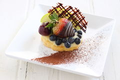 Fruit tart. With fresh fruit like strawberry chocolate coating, blueberry,  cherry, styling with chocolate piece and cocoa powder Royalty Free Stock Photography