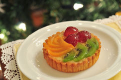 Fruit tart cake. On a white plate, christmas background Royalty Free Stock Photo