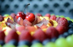 Fruit tart - a close-up of cherries and other fresh fruits royalty free stock image