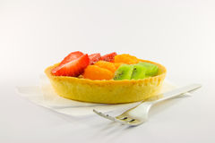 Fruit Tart with Fork. Strawberry, mandarin and kiwi custard fruit tart on a napkin with fork on a  white background Stock Images
