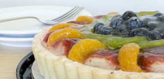 Fruit tart with fork and plates. Close up of a delicious fruit tart with thick glazing with plates and fork in the background Stock Image